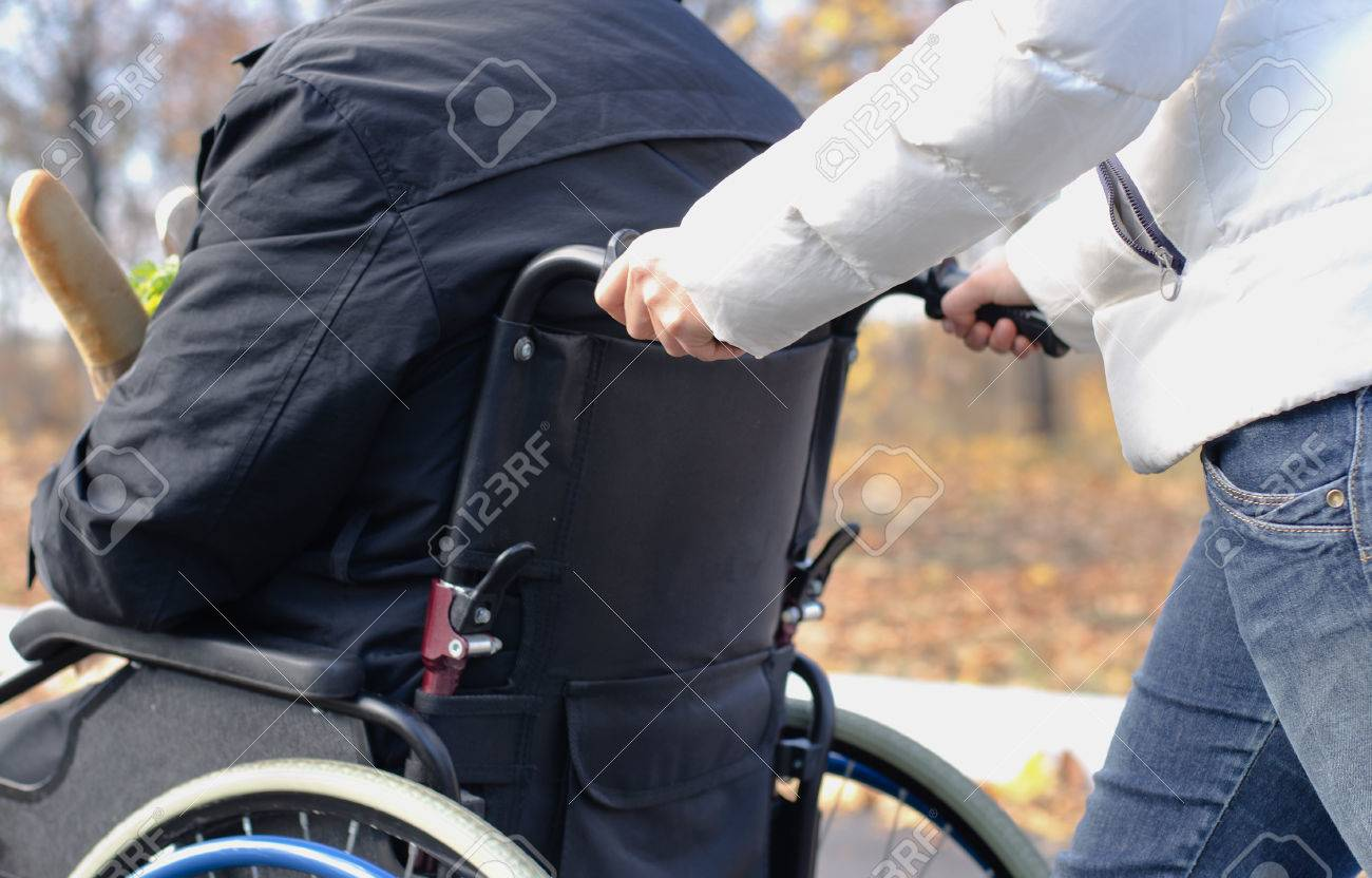 Close up view of the hands of a woman pushing a disabled man in a wheelchair along a rural street in the sunshine - 23387905