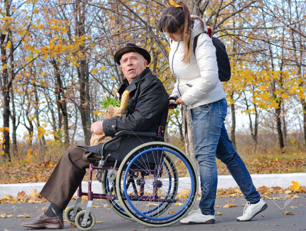 Woman pushing an elderly handicapped man in a wheelchair along a rural street as they return from doing the grocery shopping together - 25984879