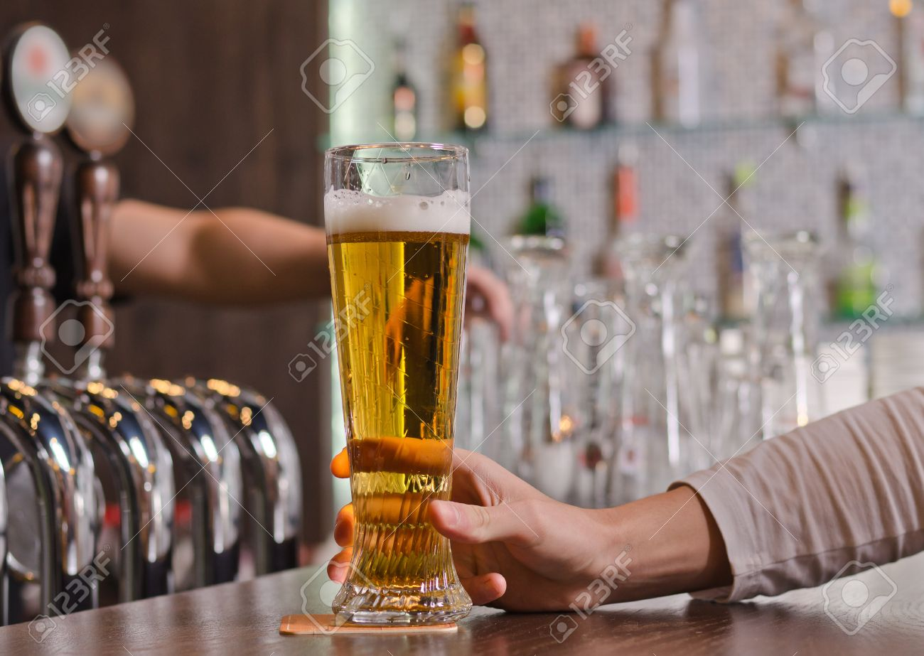 Man sitting at a counter in the bar holding a full pint glass of beer, close up view of his hand with the taps for dispensing draught beer alongside - 23833411