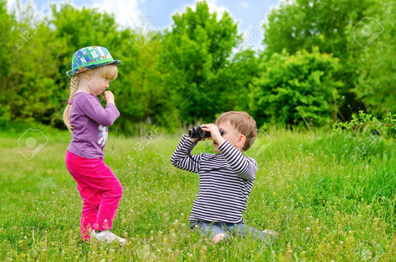 Little girl and boy playing with binoculars sitting in a green grassy field as they enjoy an educational day exploring and learning about nature Stock Photo - 29033090