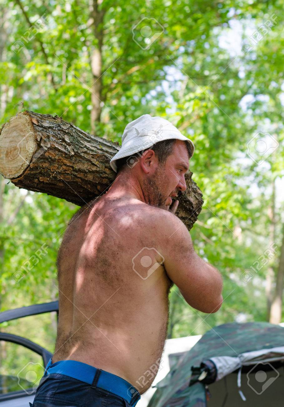 ed543ef6aa5 Shirtless strong muscular man carrying a large log of wood walking across  in front of the
