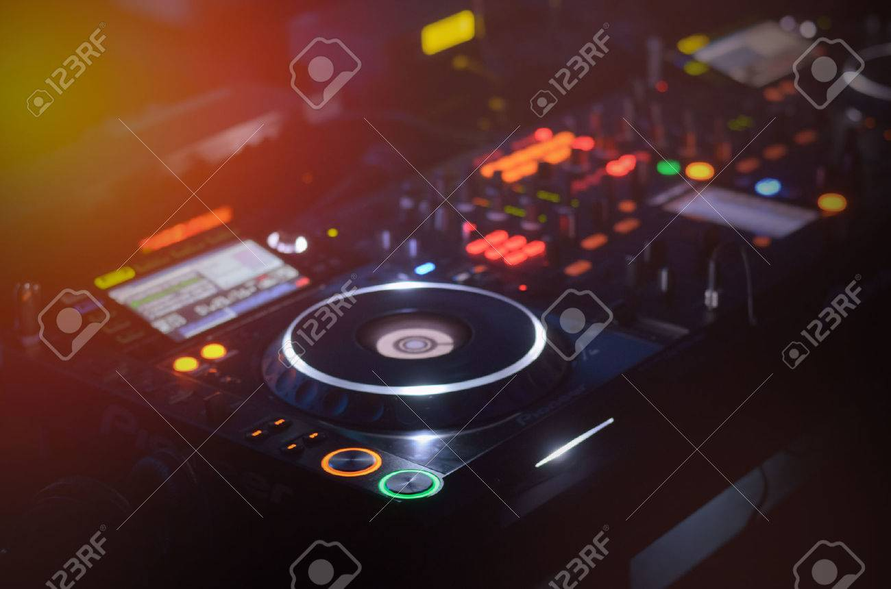 Disc Jockey mixing deck and turntables at night with colourful illuminated controls for mixing music for a party or disco - 29597564