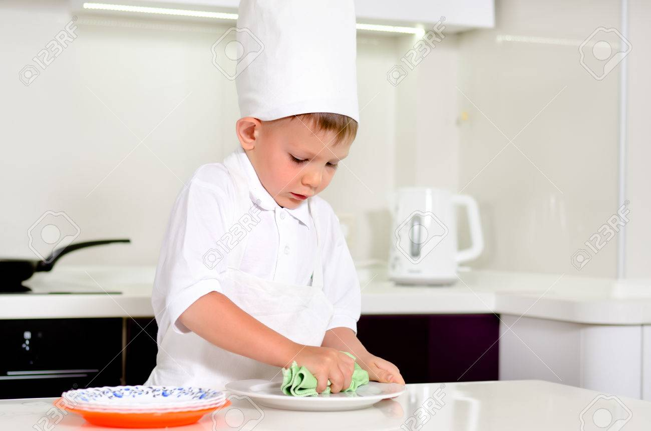 Little Boy Chef Cleaning His Plates While Cooking In The Kitchen ...