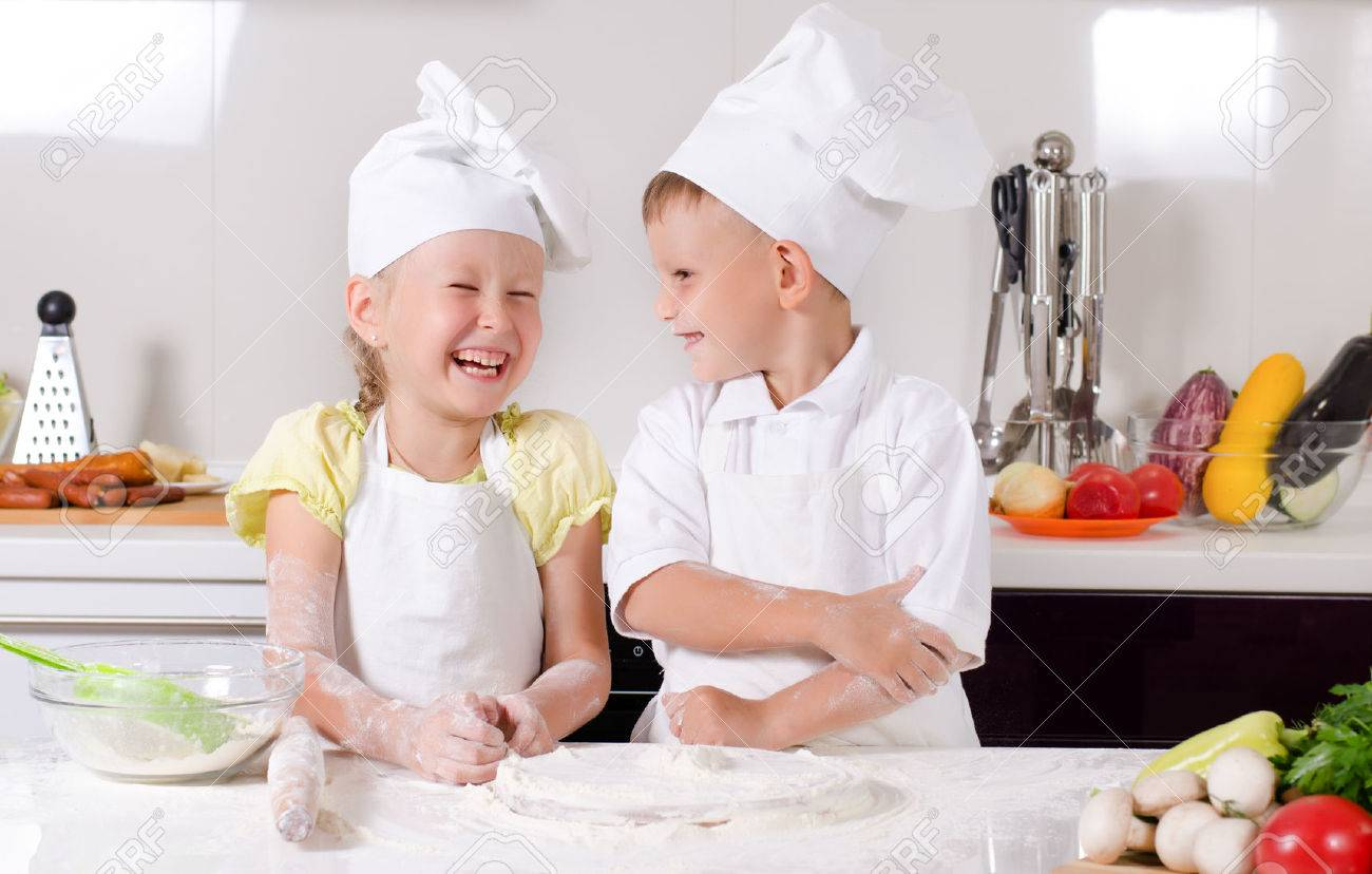Supercilious little boy chef standing proudly with folded arms looking down on a cute little girl also in chefs uniform - 30405461