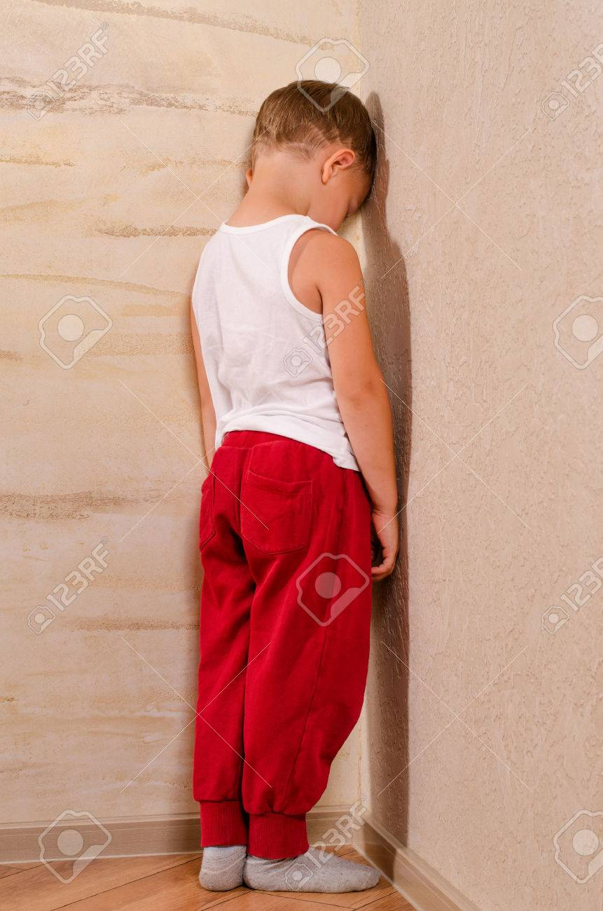 Little boy standing in a corner sulking turning to watch behind him with an angry morose expression, black and white portrait - 31182476