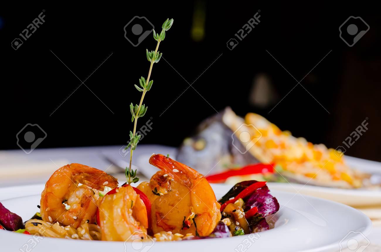 Parrillada De Langostinos Rosa Sin Cáscara Y Vieiras Con Arroz Y Verduras Que Se Sirven En Una Mesa De Restaurante Con Fondo Oscuro Y Copyspace