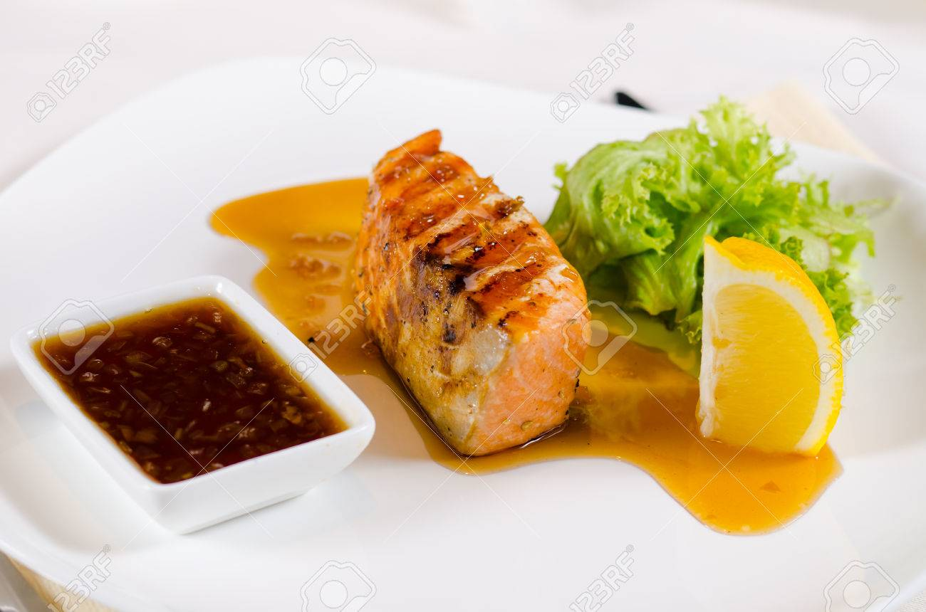 Plated Meal Of Grilled Salmon With Sauce And Garnish Served In