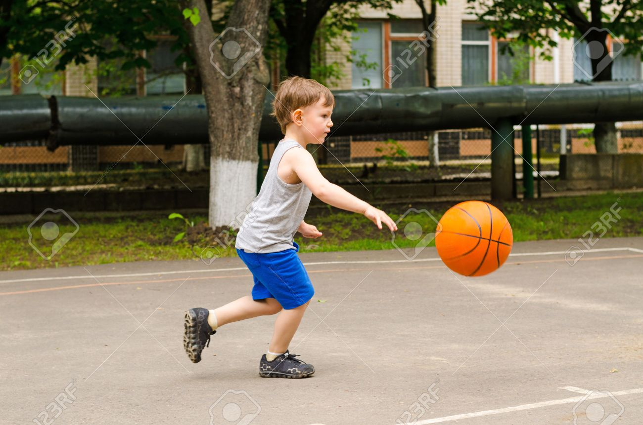 Little boy playing basketball running along the court in his sports wear bouncing the ball, side view outdoors - 34203229