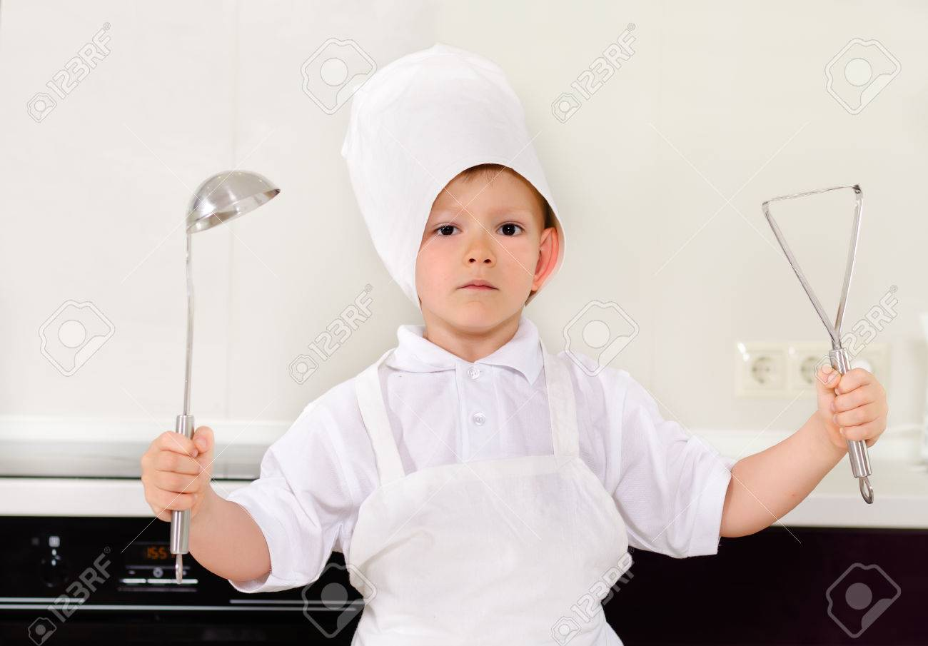 Proud Little Boy Chef In A White Toque And Apron Holding Up A ...