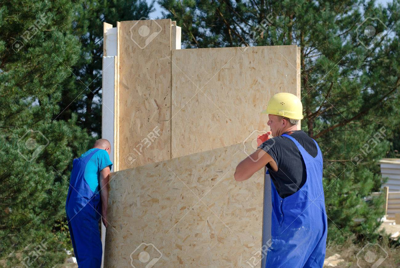 Team of builders on site carrying an insulated wooden wall panel