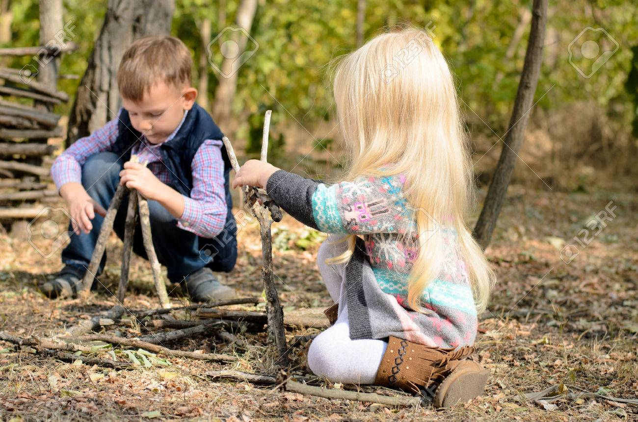 Stylish little boy and girl playing in woodland with sticks happily crouching together on the ground building different structures - 36616870