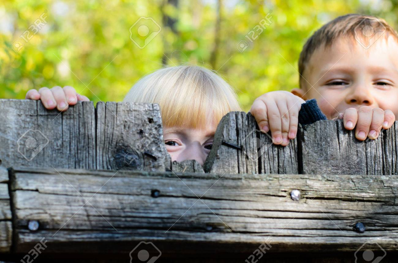 Two children, a little blond girl and boy, standing side by side peeking over an old rustic wooden fence with just their eyes visible - 36617030