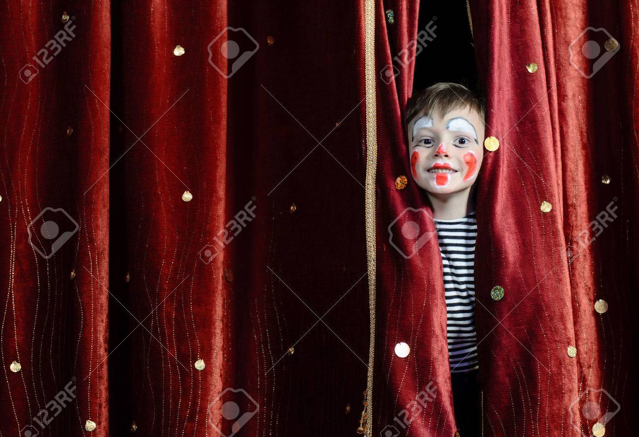 Young Boy Wearing Clown Make Up Peering Out Through Opening in Red Stage Curtains - 39420029