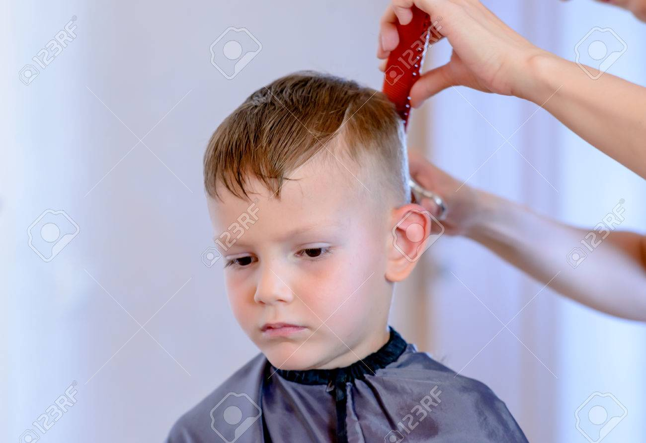 Hairdresser Cutting A Little Boys Hair Into A Short Hairstyle