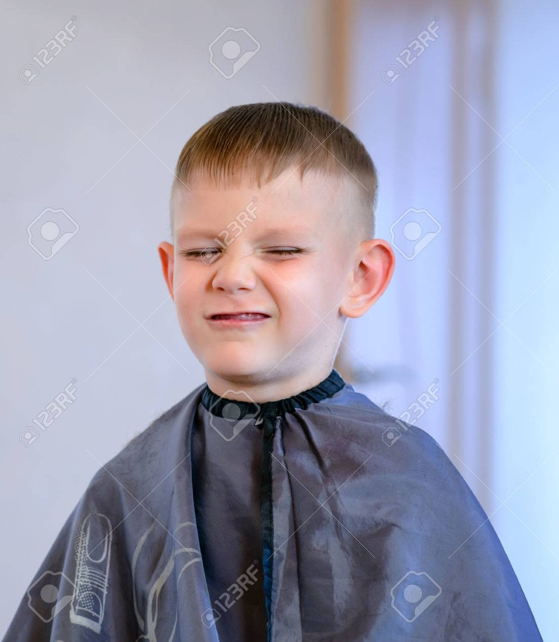 Young Boy Grimacing With Eyes Closed While Getting Hair Cut