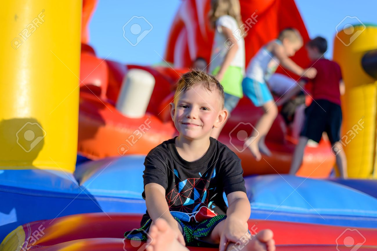 Smiling happy barefoot little boy sitting on a colorful inflatable plastic jumping castle at a fairground or kids playground - 41912277