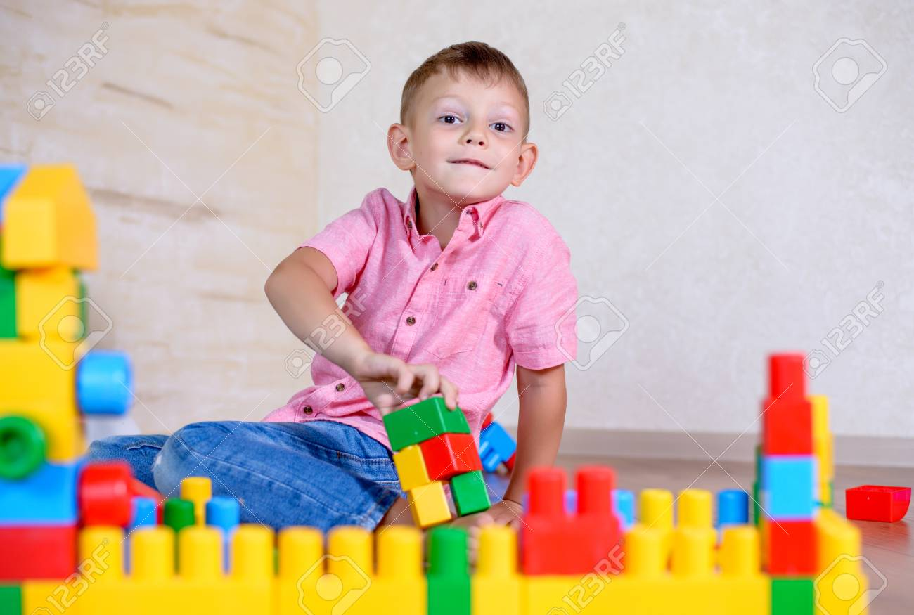 0431a076f Cute cheeky young boy playing at home with colorful plastic building blocks  holding up a toy