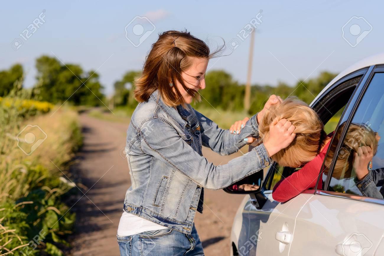0970e3b4f7de64 Standard-Bild - Zwei Frauen kämpfen auf der Straße auf einer Landstraße mit  einer Innenseite und einer Außenseite des Autos kämpfen durch das offene  Fenster ...
