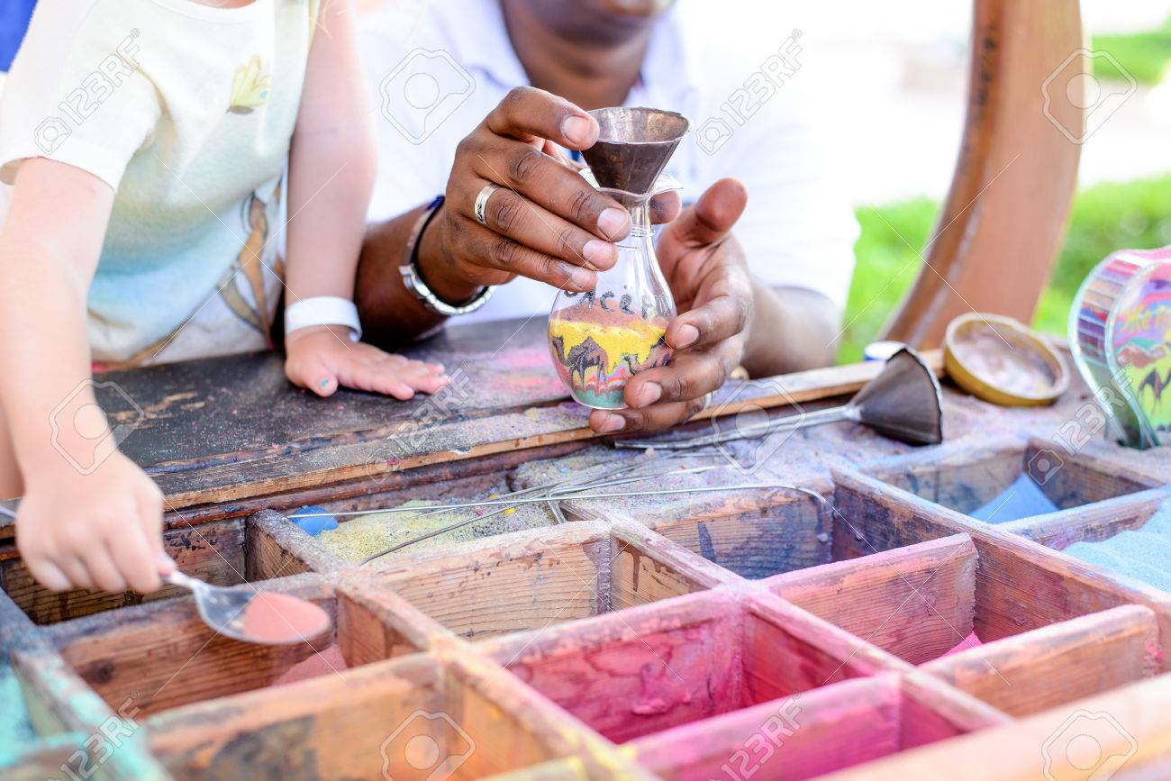 Boy creating colorful sand art filling a see-through container with assorted colored pigments at an outdoor display - 44057315