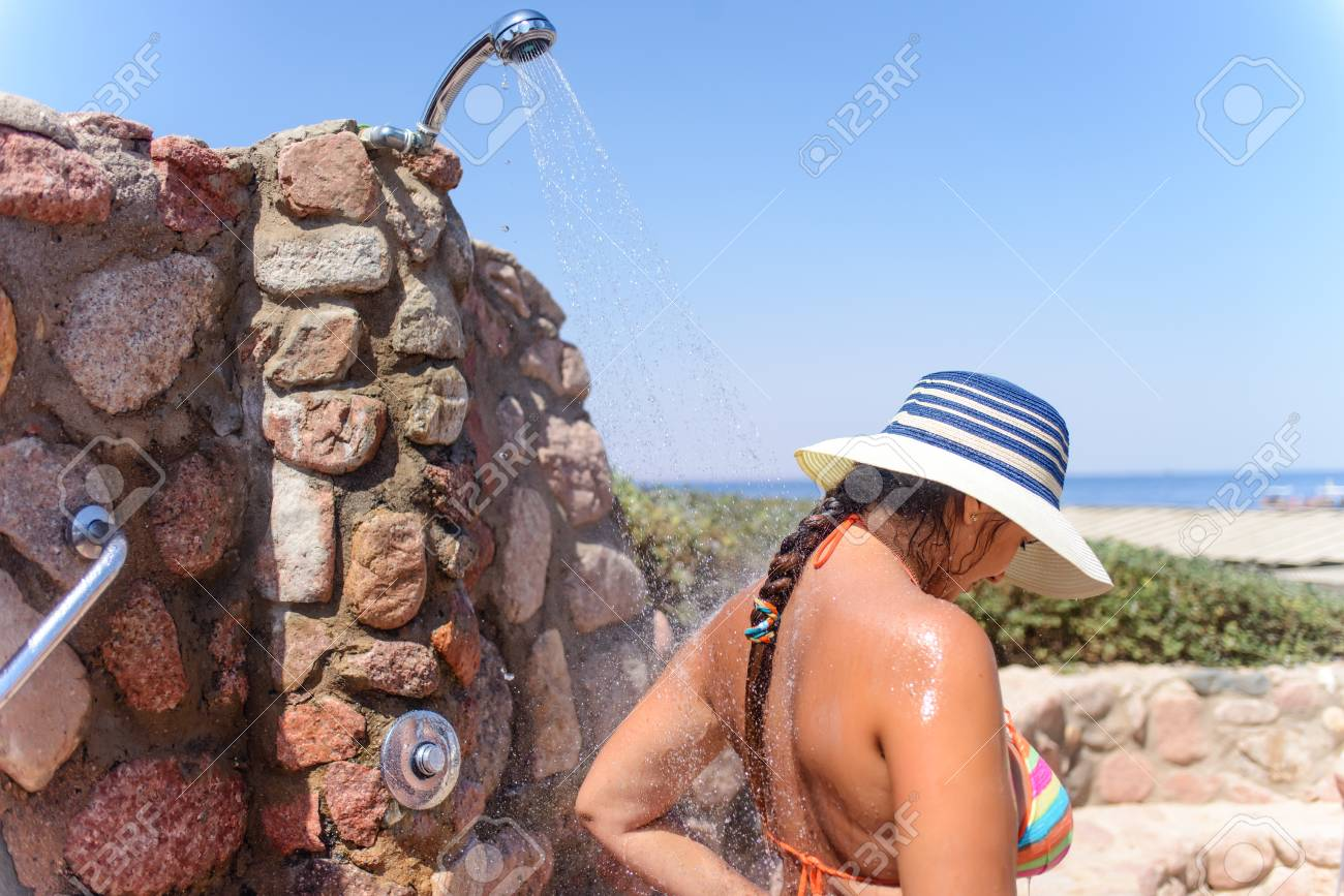 Woman Showering At An Open-air Shower Attached To A Stone Wall ...