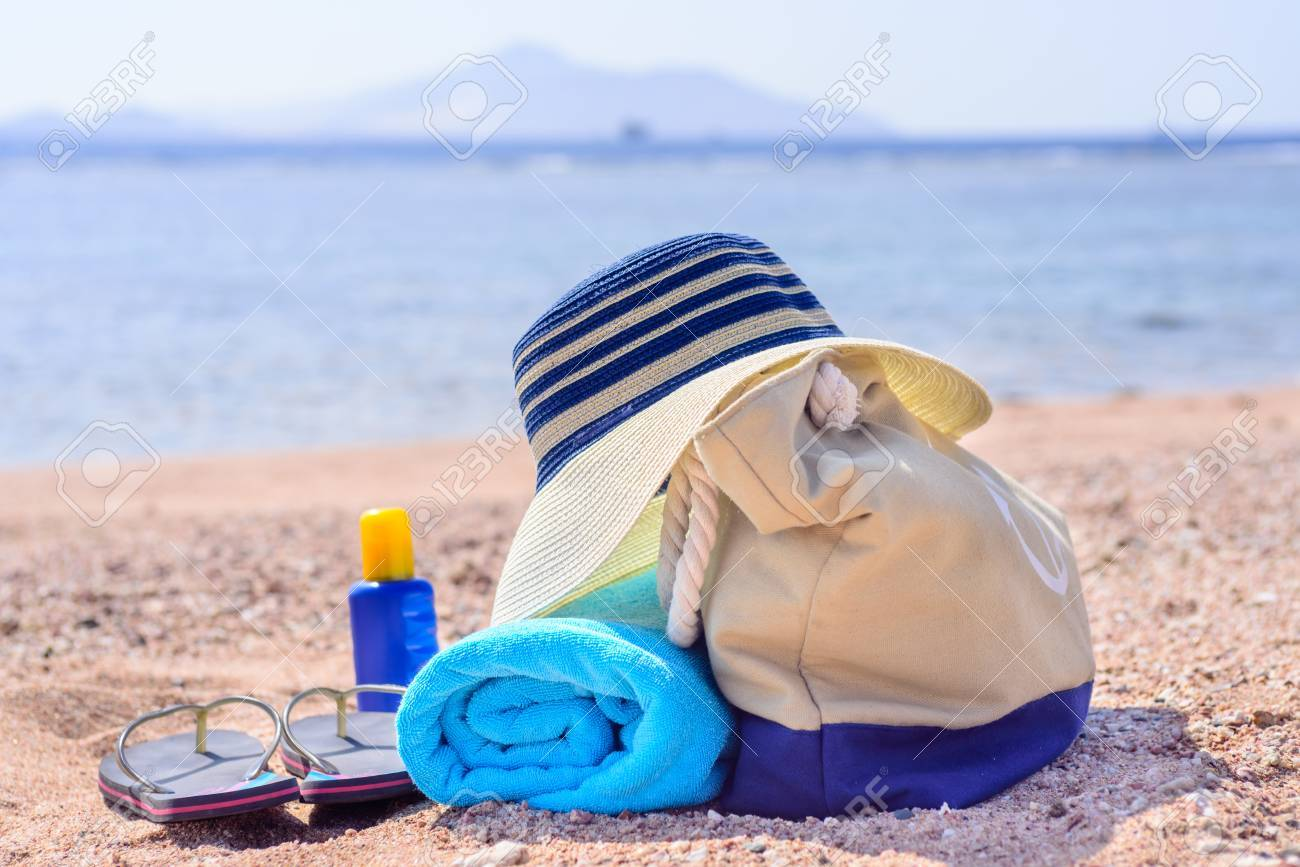 9e06cad73b60a Standard-Bild - Strandtasche und Zubehör für Tag am Strand am Ufer mit  Verlassener Strand im Hintergrund - Sonnenhut
