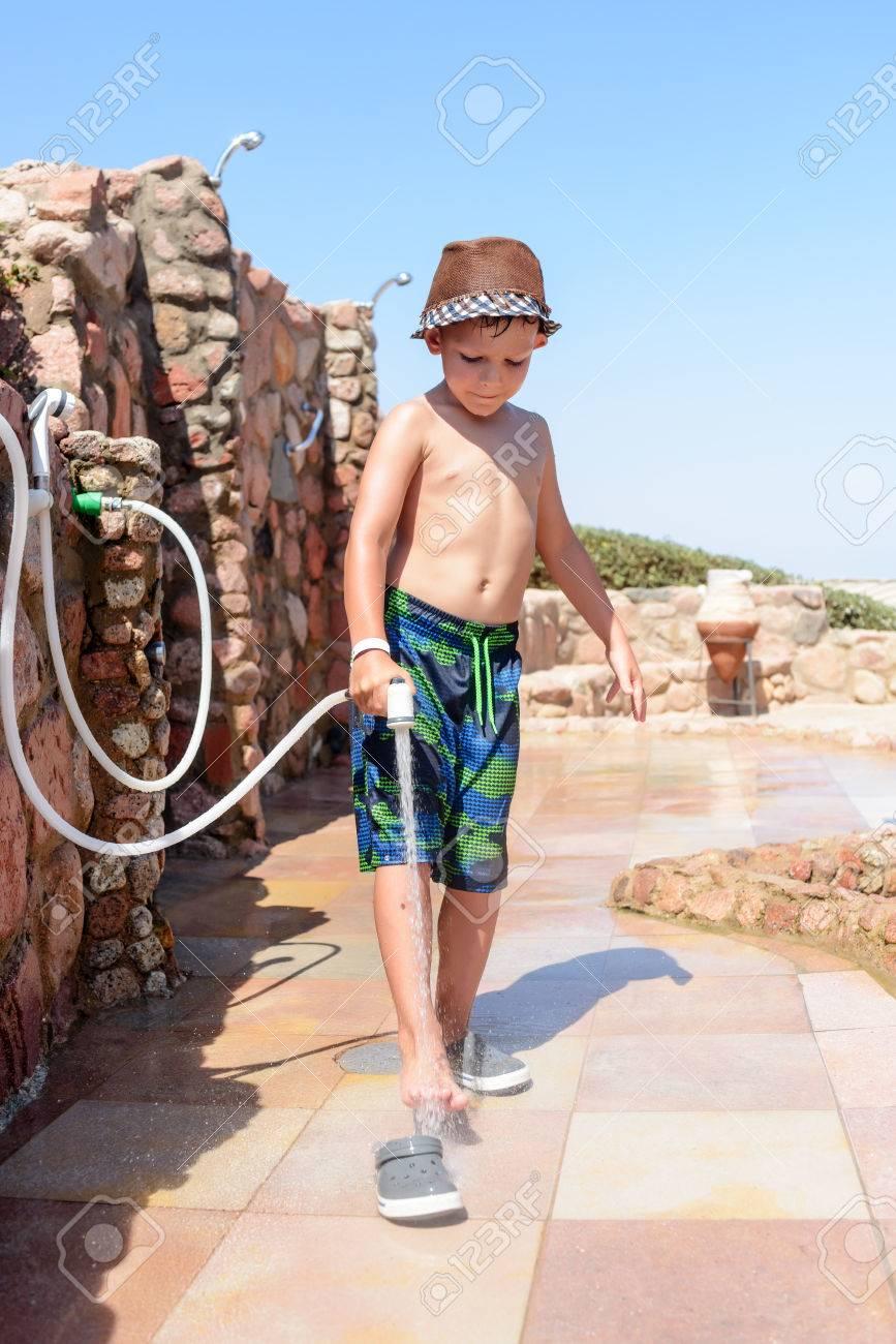 Enjuagar Playa En Pies Manguera Centro Joven Con La Un Permanente Y Estilo Baño Después De Traje Chico Moda Visitar Sombrero Los Una tdhCsQr