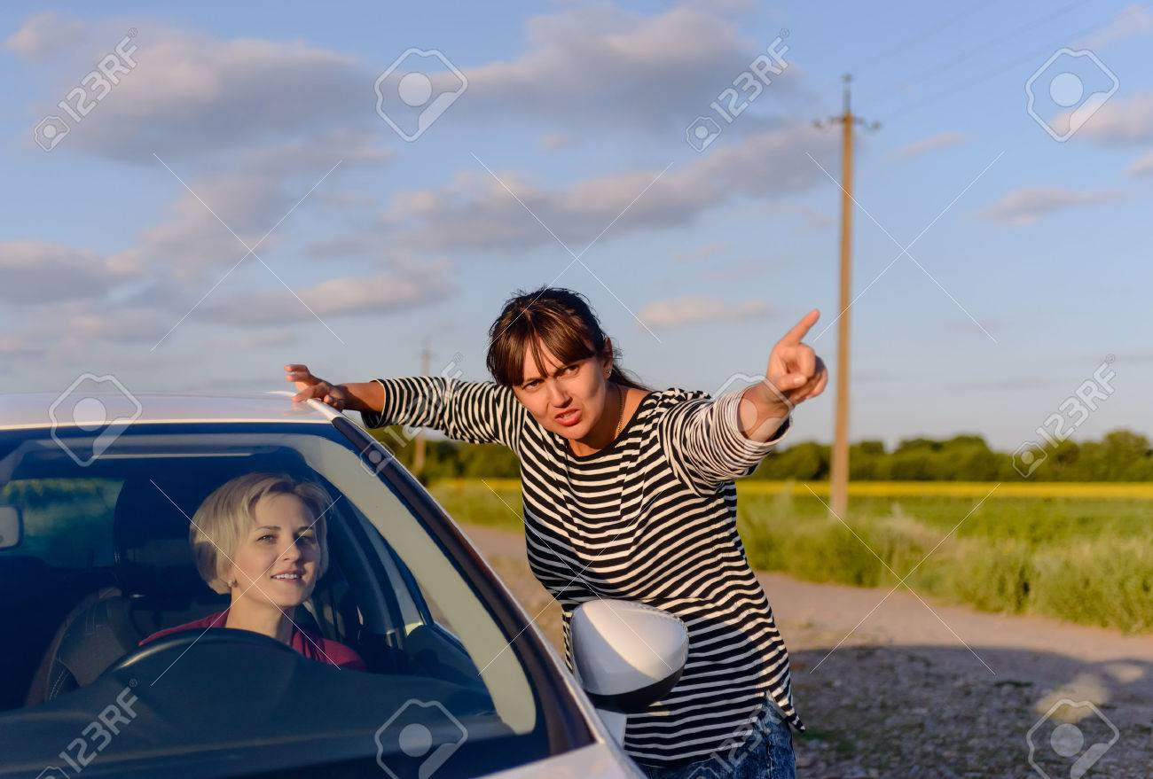 Woman giving directions to a lost woman driver on a rural road