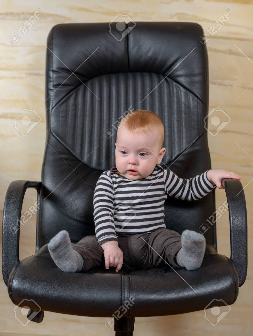 Black child sitting in chair - Fun Portrait Of A Cute Chubby Little Baby Boy Sitting In A Black Leather Office Chair