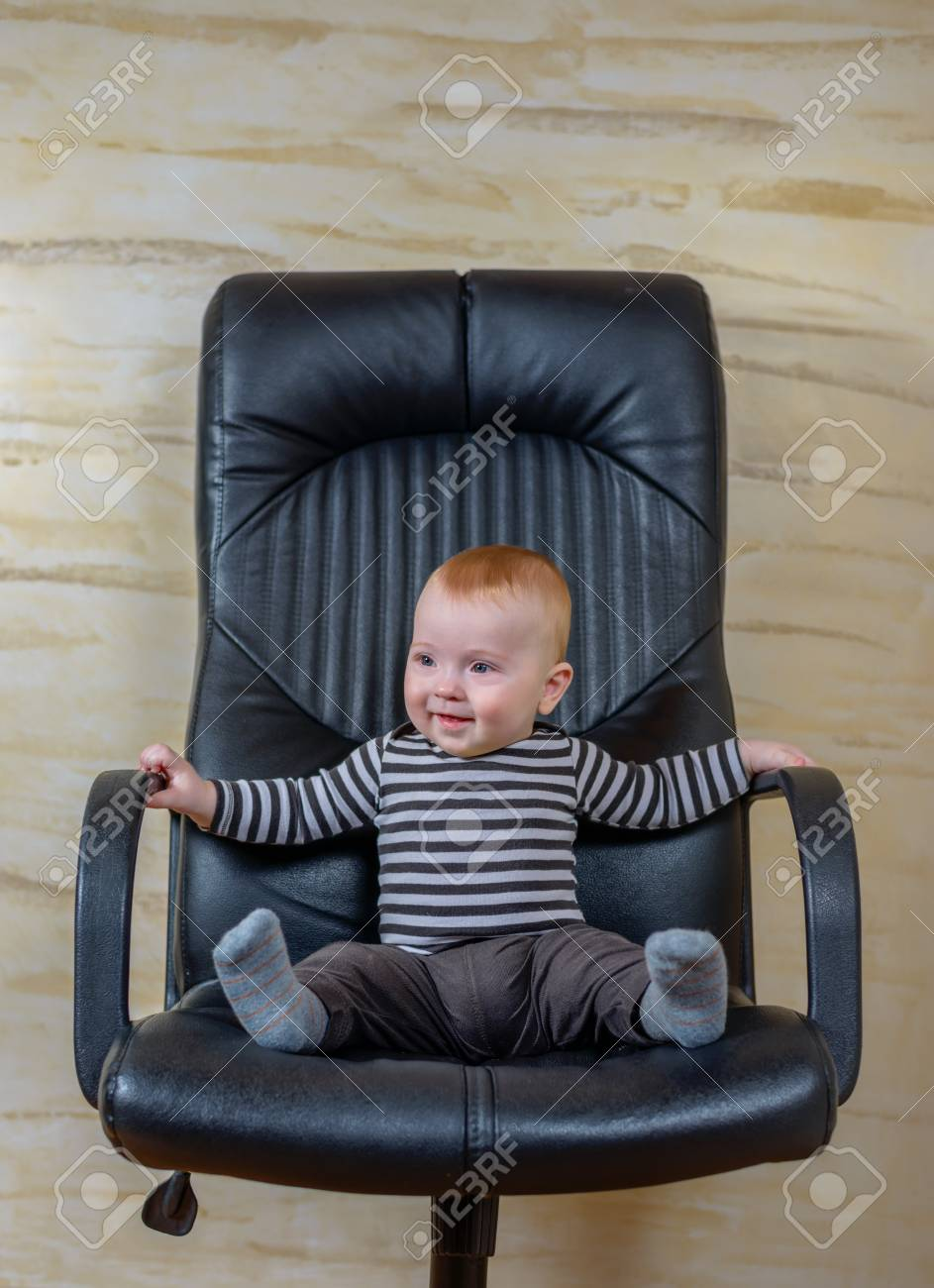 Awe Inspiring Cute Baby Boy Sitting On Black Office Chair And Looking Away Interior Design Ideas Apansoteloinfo