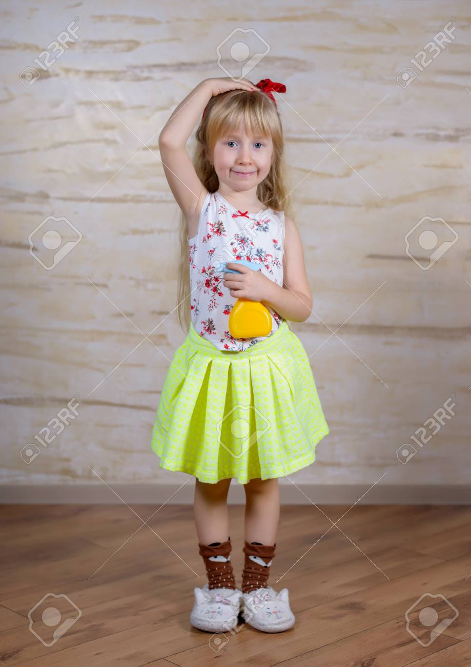 Single cute little girl in long blond hair squirting water in the air with  yellow and