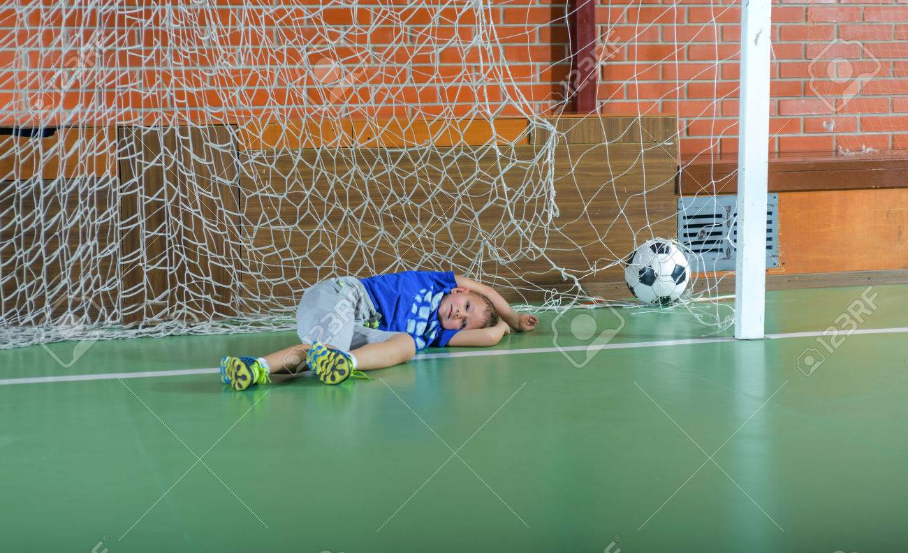 Stock Photo   Young Goalie Saving A Goal On An Indoor Soccer Court Lying  Across The Goals On His Side Clutching The Ball