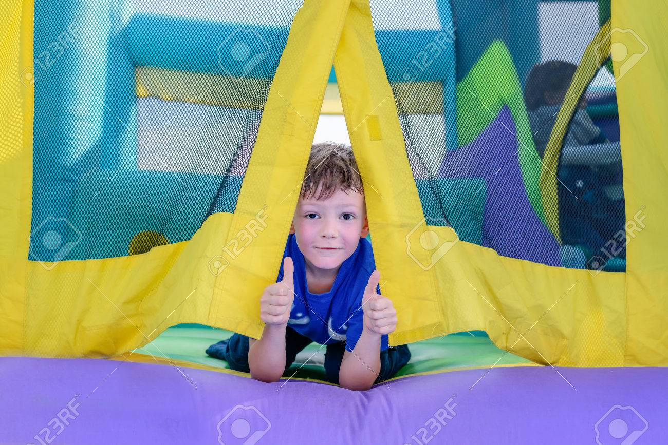 Single cute little curious boy with sweaty face looking from entrance of bouncy house - 56119450
