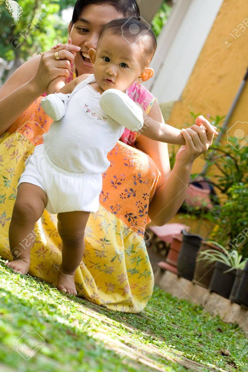14ee1c1ea Cute Asian Baby Girl Learning To Walk Assisted By Her Mother Stock ...
