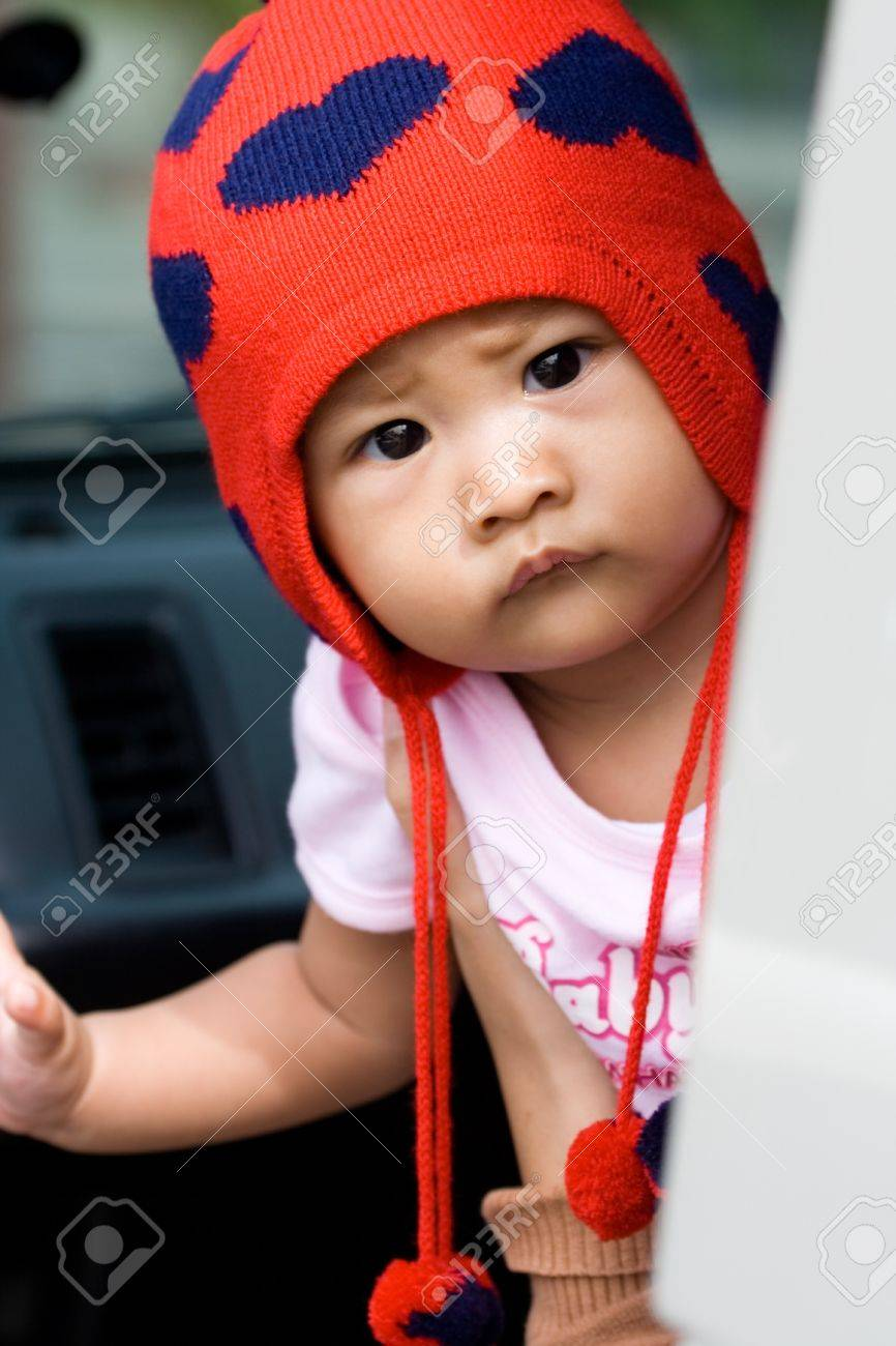 cute baby girl looking curiously (questioning) onto something from inside of a car - human expression Stock Photo - 4237570