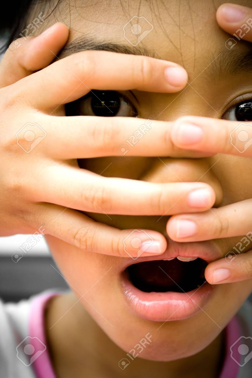 little girl looks surprising and terrified onto something she saw. putting her fingers over her face. Stock Photo - 4846595