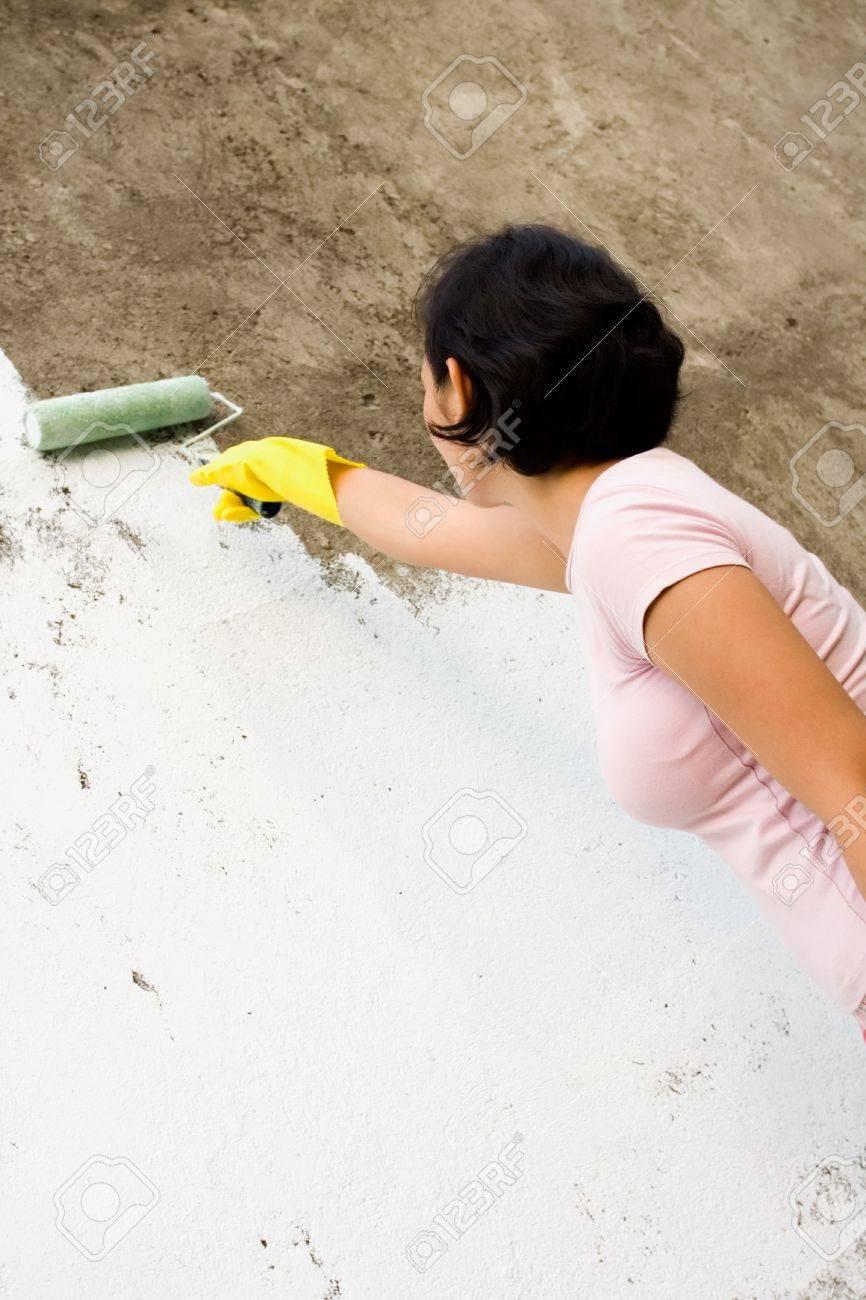 Indépendant Asiatique Jeune Femme De Peinture Du Mur Extérieur De Sa Maison Avec Une Peinture De Couleur Blanche à L Aide D Un Rouleau Et Des Gants