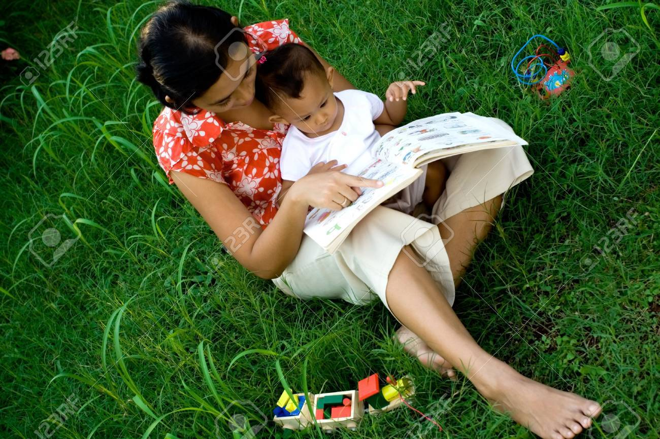 asian mother teaching her 1 year old baby girl using educated books and toys in the park Stock Photo - 5012587