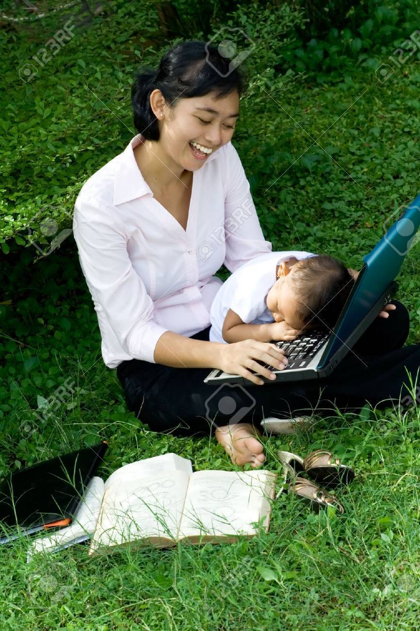 patience of a mother: asian mother still seems to have enjoyment being bothered by her baby girl while doing her works Stock Photo - 5096770