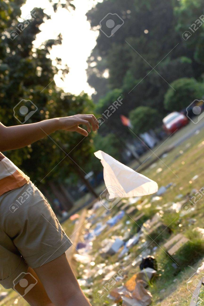 environmental pollution issue concept of a person involved in environmental damage. hand throwing trash (tissue) to an already messy parking lot full of people's waste everywhere. Stock Photo - 5154537