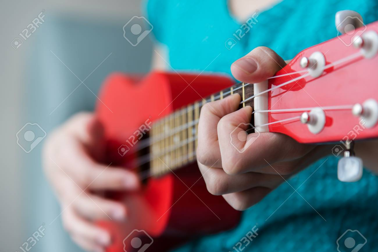 Close Up Of Girls Hand Playing Chords On A Red Soprano Ukulele