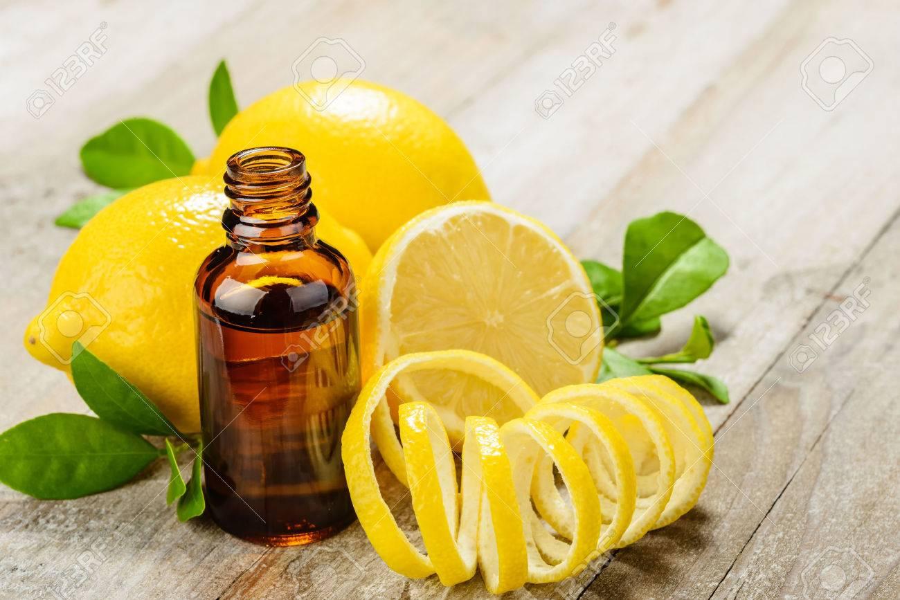 lemon essential oil and lemon fruit on the wooden board - 43695581