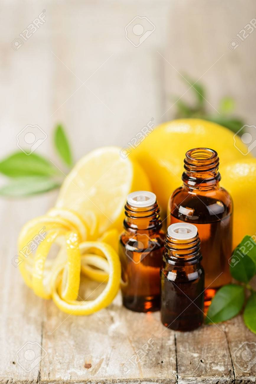 lemon essential oil and lemon fruit on the wooden board - 43695525