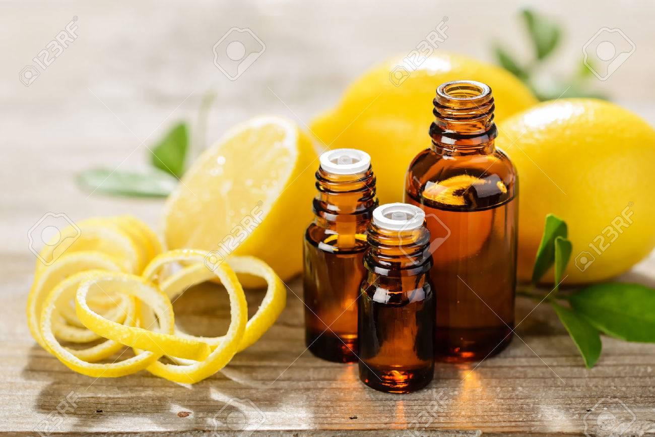 lemon essential oil and lemon fruit on the wooden board - 43693280