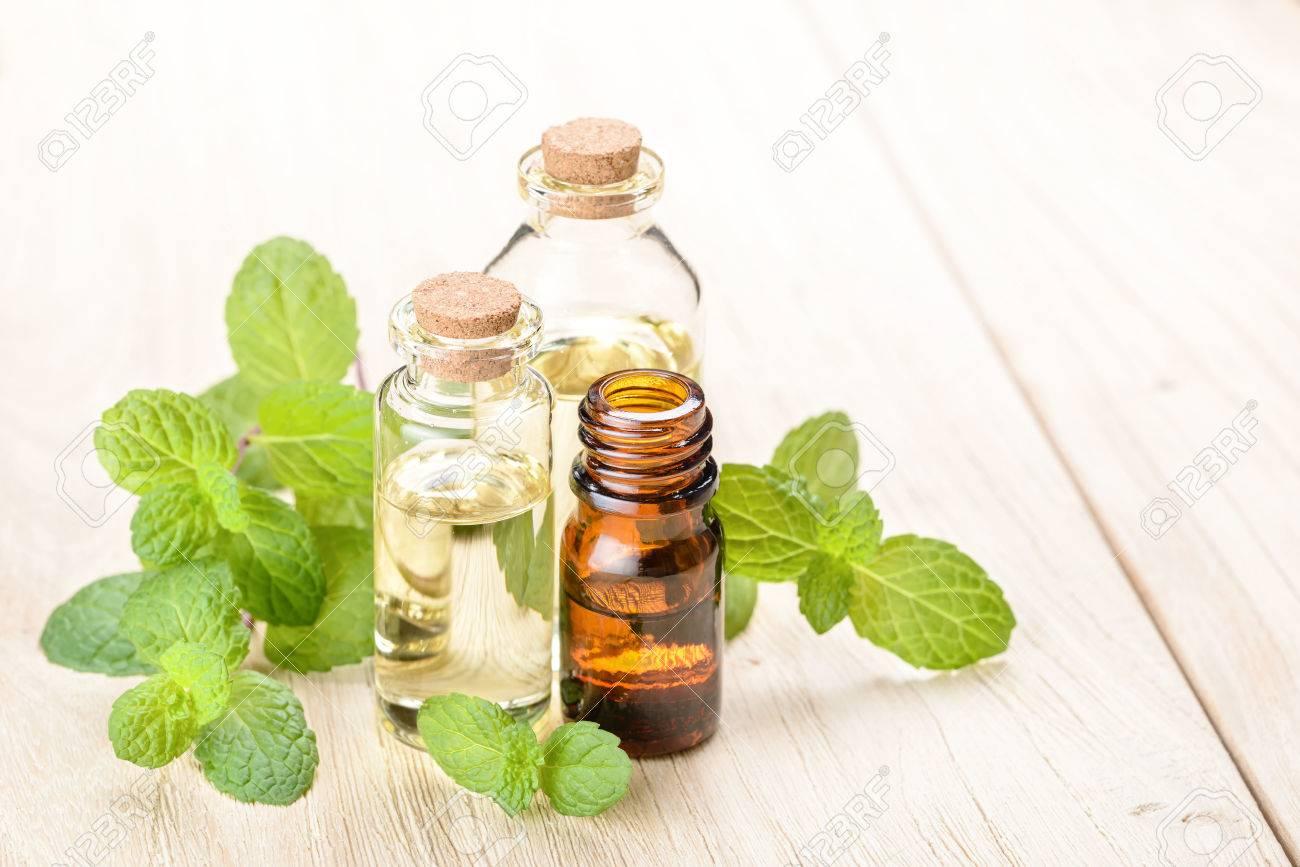 fresh mint essential oil on wooden board - 52433268