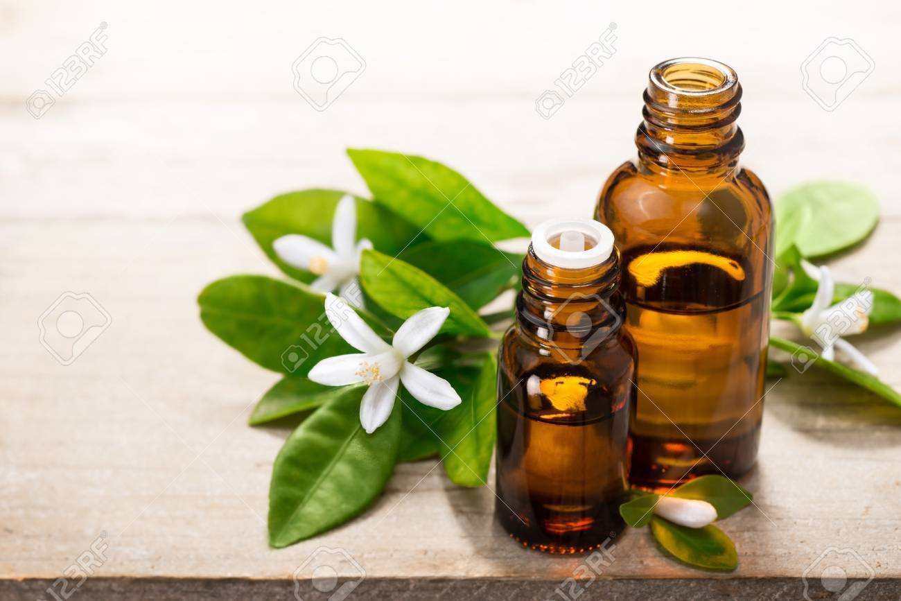 neroli essential oil in the brown glass bottle, with fresh white neroli flower and green leaves. - 73793175