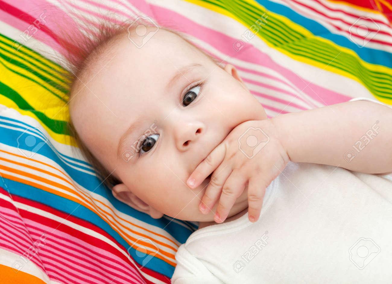 Retrato De Un Hermoso Bebé De 6 Meses Acostado En La Cama Y Chuparse ...