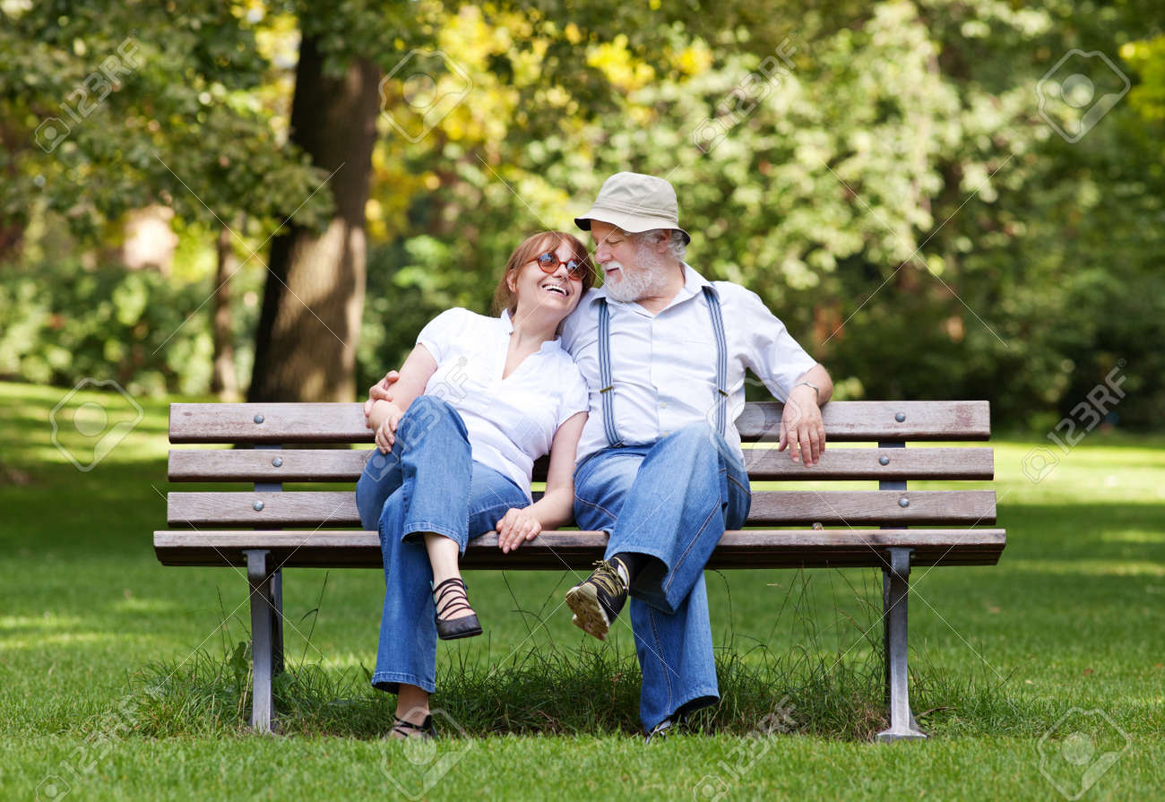 Senior Couple Sitting On A Park Bench Hugged Shallow Depth Of