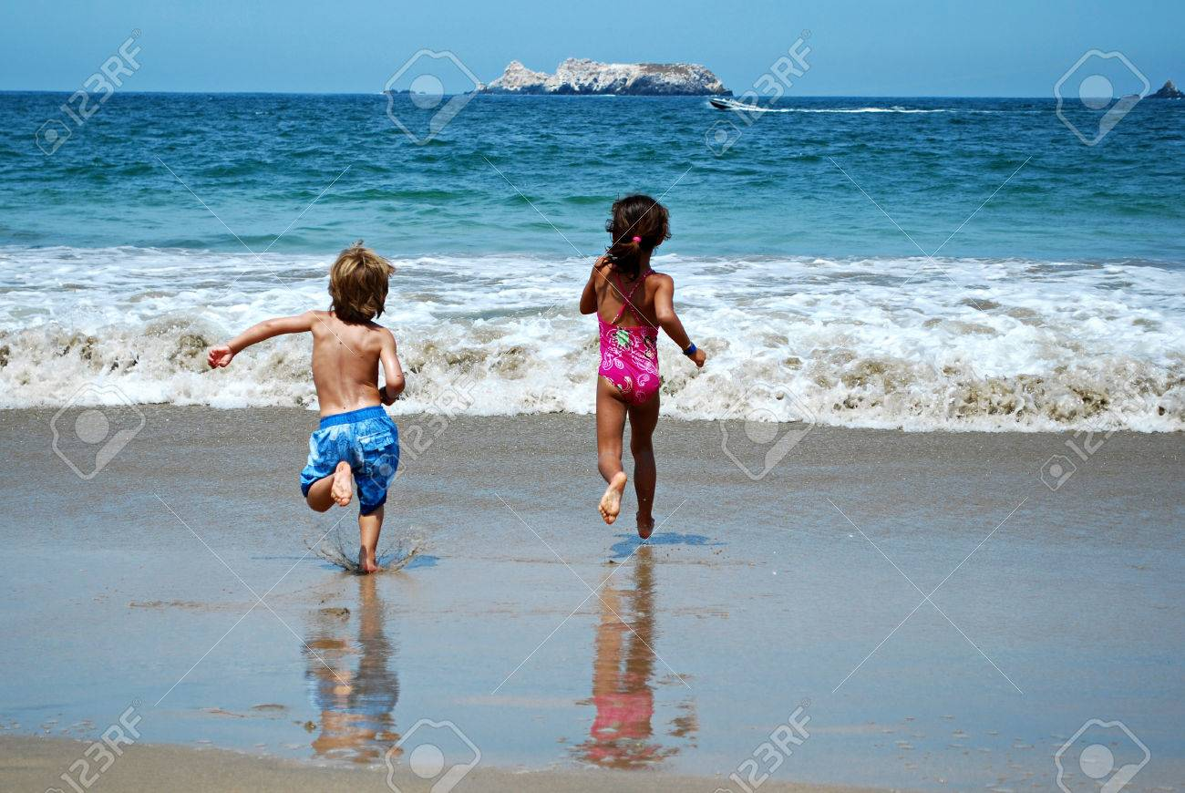 Picture Of Kids Running To Swim On Beach Stock Photo
