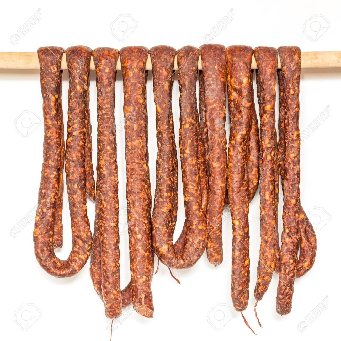 Row of smoked pork sausage in natural casings hanging on a wooden