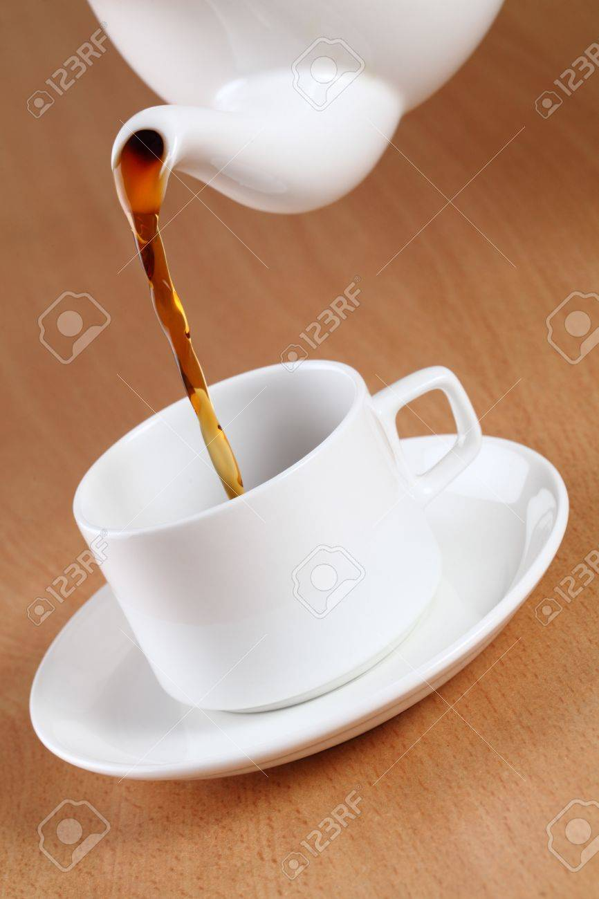 Teapot pouring tea into a cup. Stock Photo - 12225371